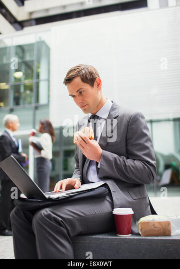 Businessman eat lunch and working outside office building - Stock Image