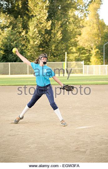 Teenager pitching soft ball. - Stock Image