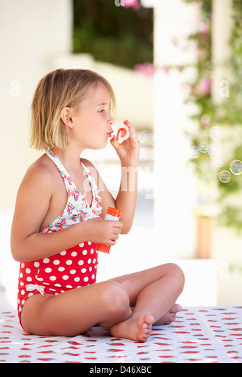 Girl Wearing Swimming Costume Blowing Bubbles - Stock Image