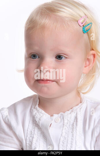 Portrait Of A Blond Toddler Girl With A Timid Expression on white background - Stock Image