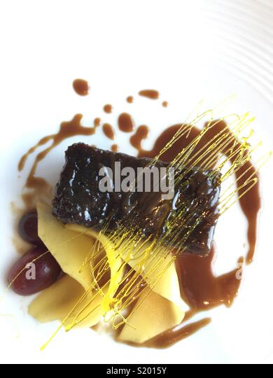 Beautifully presented dessert of sticky toffee pudding with spin sugar decoration and fruit - Stock Image