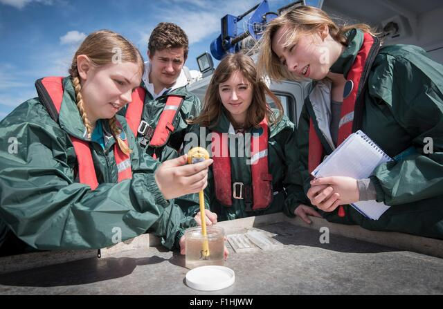Student marine biologists test sea water sample on research ship - Stock Image