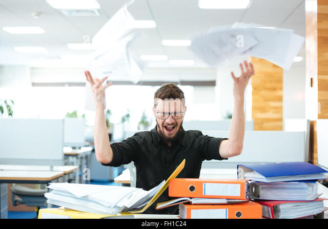 Angry businessman sitting at the table and shouting in office - Stock Image
