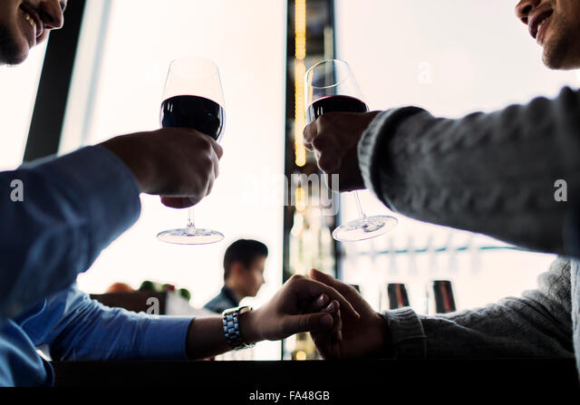 Low angle view of gay men toasting red wine glasses at bar counter - Stock Image