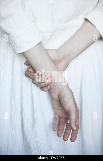 Rear view of woman holding hands behind her back - Stock Image