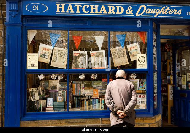 UK, England, Yorkshire, Haworth 40s Weekend, Main Street, visitor looking in Hatchard's nostalgic bookshop window - Stock Image