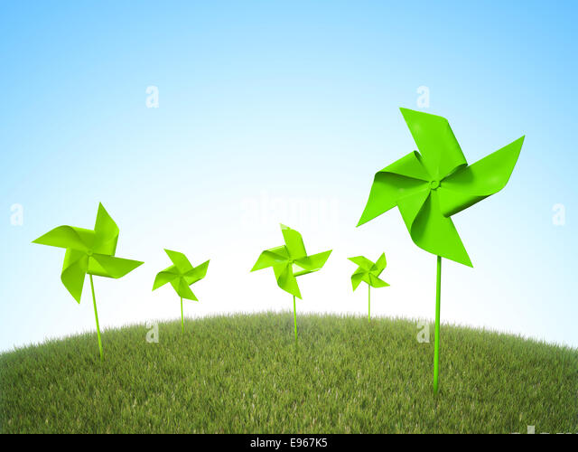 Pinwheel windmills in a field of grass - renewable energy concept - Stock Image