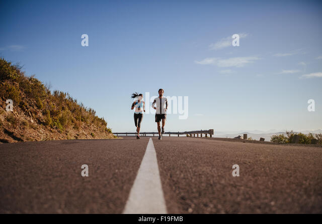 Low angle view of two young people running on road. Young couple jogging together on country road on summer day - Stock Image