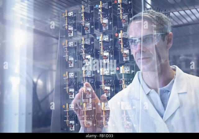 Scientist inspecting test lithium ion batteries in heat chamber in battery research facility - Stock Image