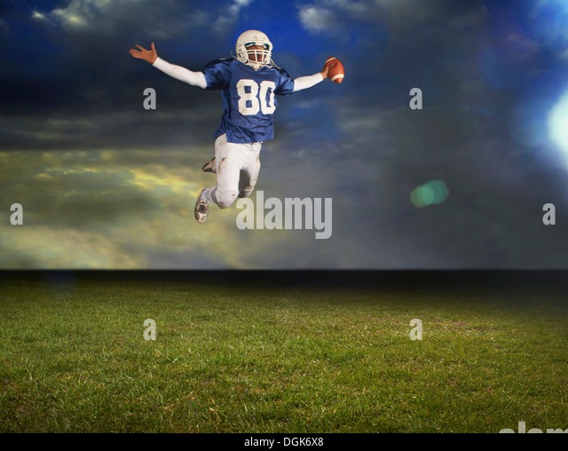 American football player mid air with arms outstretched - Stock Image