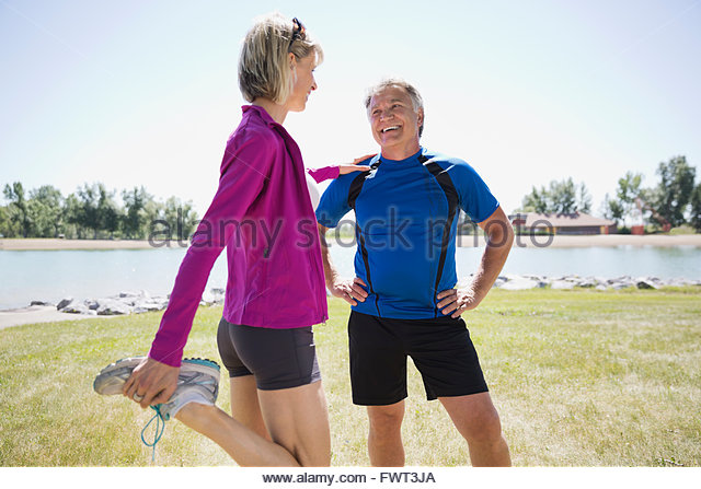Active middle-aged couple stretching by the beach - Stock Image