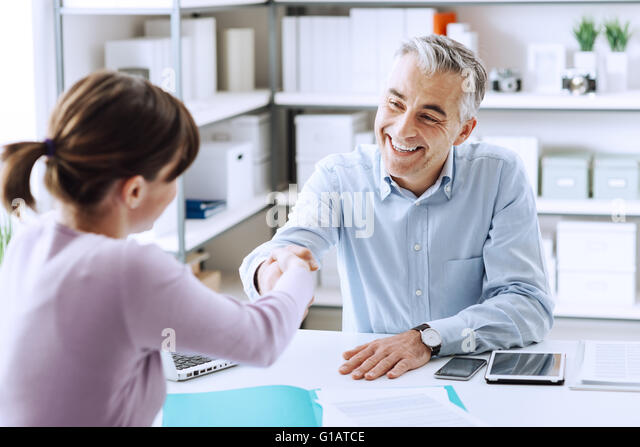 Happy young candidate shaking hands with her employer after a job interview, employment and business meetings concept - Stock Image