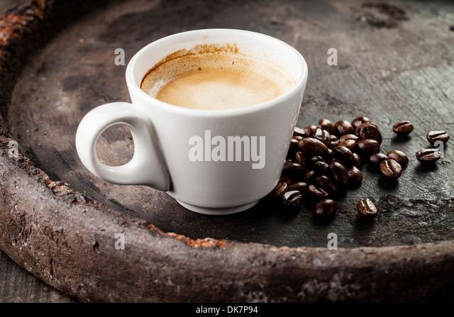 Coffee cup with coffee beans on dark background - Stock Image