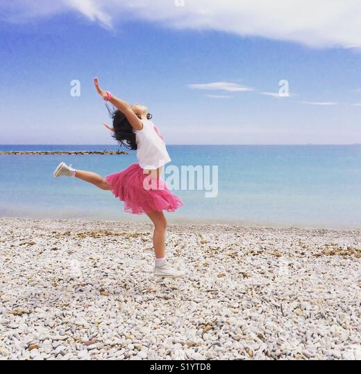 Girl in pink skirt dancing by the shore of the Mediterranean Sea - Stock Image