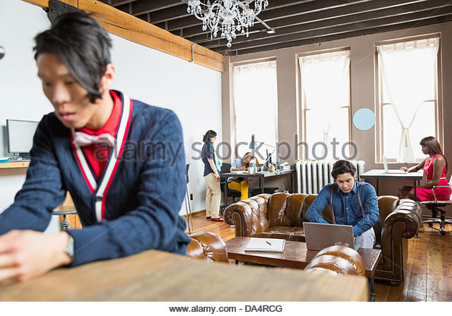 Entrepreneurs working in creative office space - Stock Image