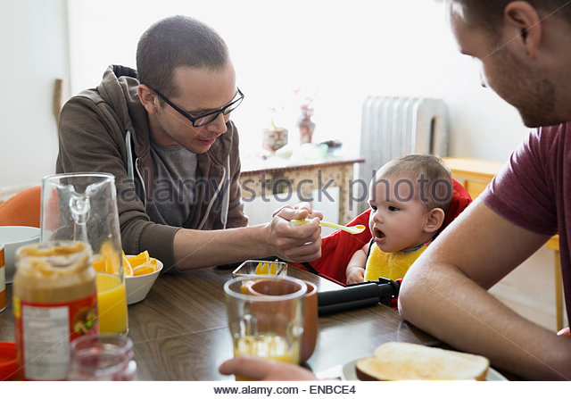 Homosexual couple feeding baby daughter at table - Stock Image