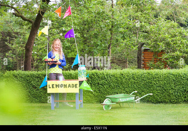 Lemonade stand girl with tray of apples behind her stand - Stock Image