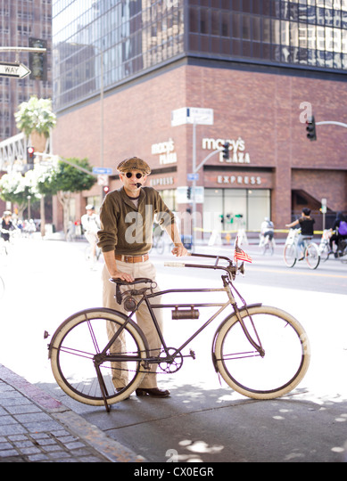 Man with Bicycle Smoking Pipe - Stock Image