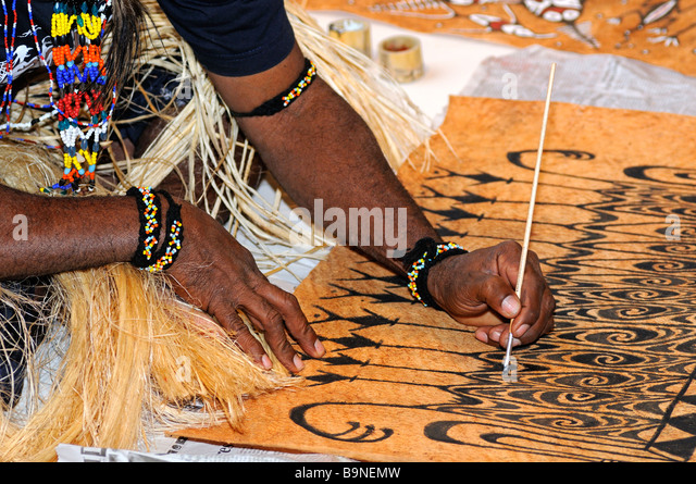 Local artist paints traditional motifs on the bark of the Khambouw tree, Lake Sentani area, West Papua, Indonesia - Stock Image