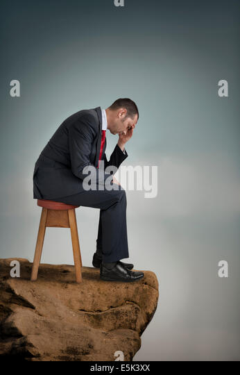 depressed businessman suffering depression on a cliff ledge - Stock Image