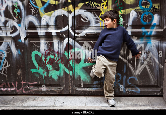 Young boy leaning against old-fashioned door covered with graffiti - Stock Image