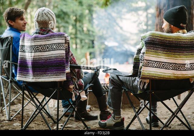 Three friends sit around a campfire in Big Sur, California. - Stock Image