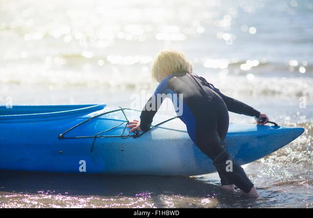 Boy in water pushing canoe - Stock Image