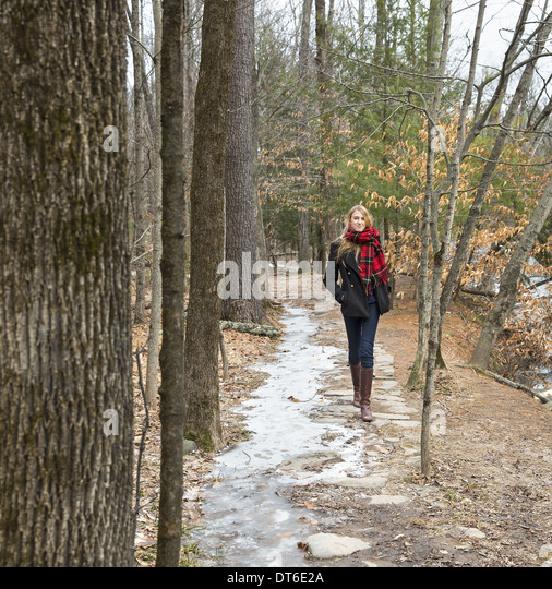 A woman in a winter coat and red scarf walking down a woodland path, in winter. - Stock Image