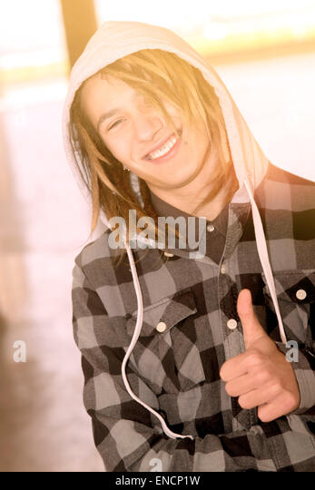 Lifestyle portrait of a young man with rasta hairs warm tones filter applied - Stock Image