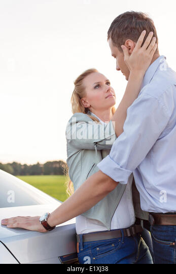 Side view of romantic young couple by car at countryside - Stock-Bilder