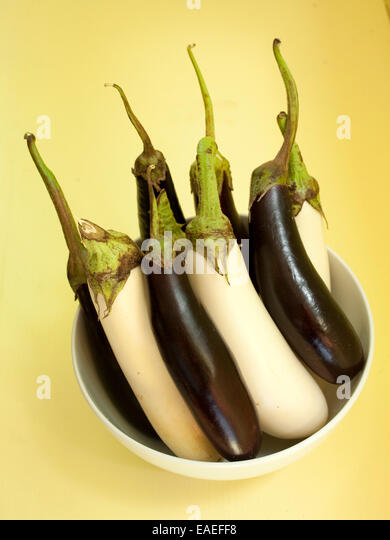 small eggplants in white bowl - Stock Image