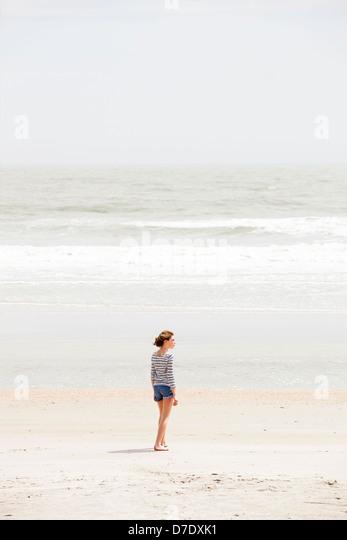 Girl looking at beach - Stock Image