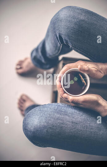Overhead view of woman sitting with cup of tea - Stock Image