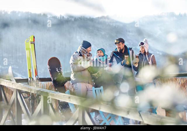 Skier friends talking and drinking cocktails on sunny balcony apres-ski - Stock-Bilder