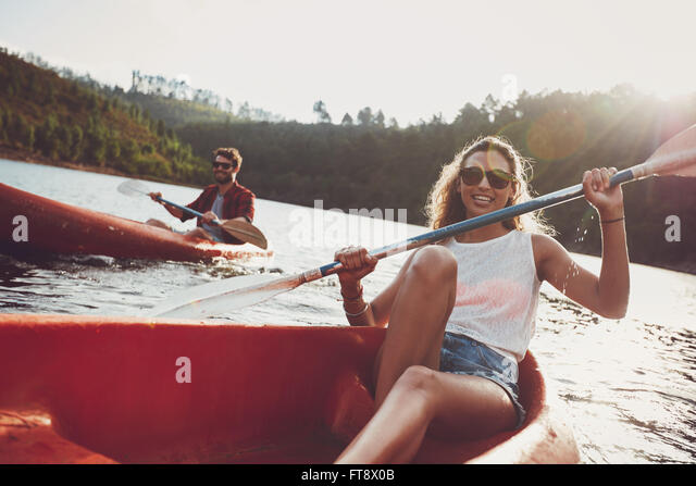 Beautiful young woman kayaking in a lake with man paddling in the background. Young couple canoeing on summer day. - Stock Image