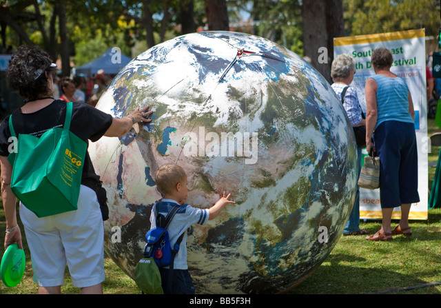 child playing with inflated world globe Earth Day Celebration Santa Barbara California United States of America - Stock Image