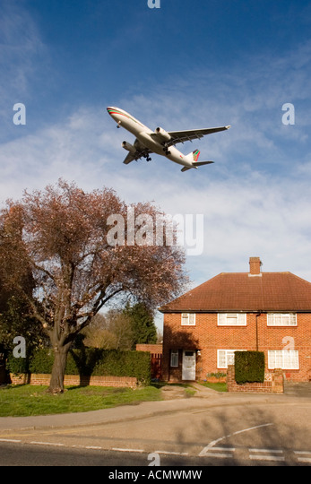 Low flying passenger airplane over houses on approach to London Heathrow airport Feltham Middlesex England UK - Stock Image