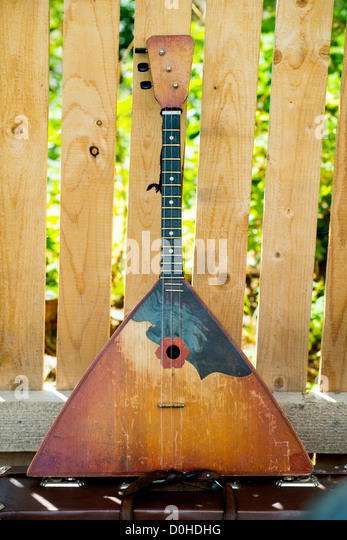 Russian balalaika a wooden fence background taken as close up. - Stock Image