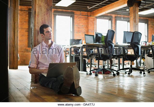 Entrepreneur working on laptop in creative office space - Stock-Bilder