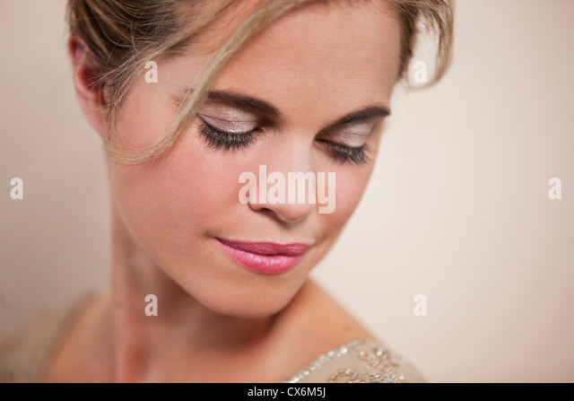 A young woman with her hair up, looking down - Stock Image