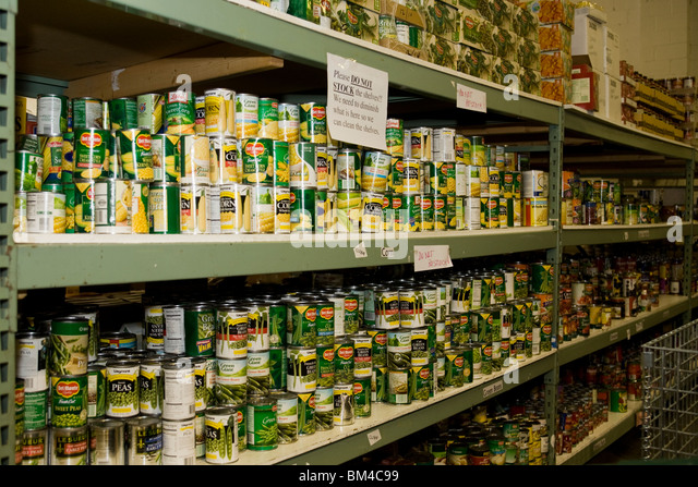 Canned food on food bank shelves - Stock Image