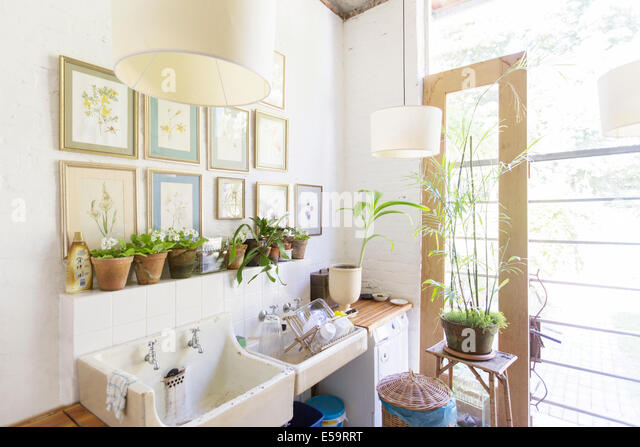 Wall hangings and lights over rustic kitchen sink - Stock Image