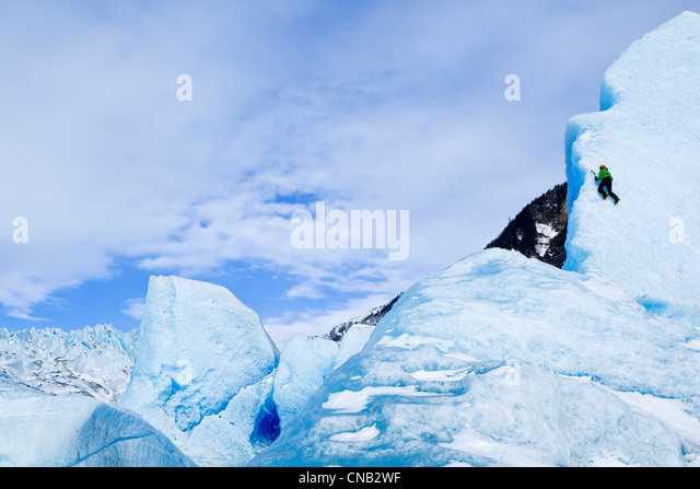 Ice climber with ice axe climbs the face of a large iceberg frozen in Mendenhall Lake, near Juneau, Southeast Alaska, - Stock Image