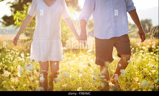 Happy and young pregnant couple hugging in nature - Stock Image