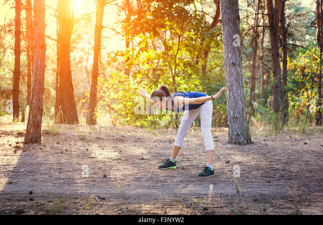 Young beautiful girl sports in the autumn forest at sunset - Stock-Bilder