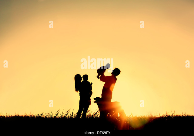 A silhouette of a happy family of four people, mother, father, baby, and child, and their dog in front of a sunsetting - Stock Image