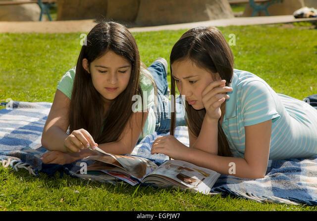 California interracial multi racial teens hang out Vietnamese-Caucasian,Hispanic Mexican girls read together. MR - Stock-Bilder