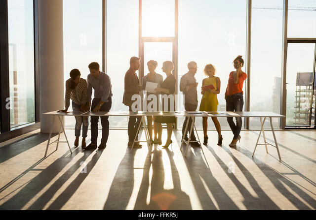 Team of architects in business meeting against urban skyline - Stock Image