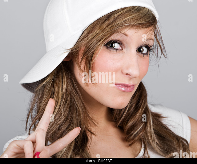 Close Up Shot of a Beautiful Teenager Girl in a White Baseball Cap - Stock Image
