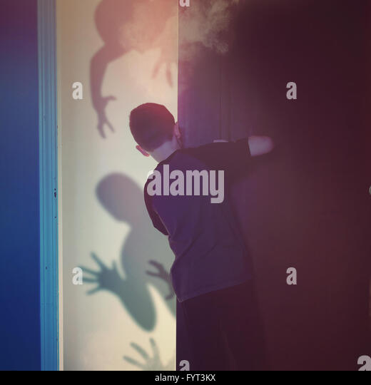 A scared child is looking inside of a closet bedroom at black evil monster ghosts in the background for imagination - Stock Image